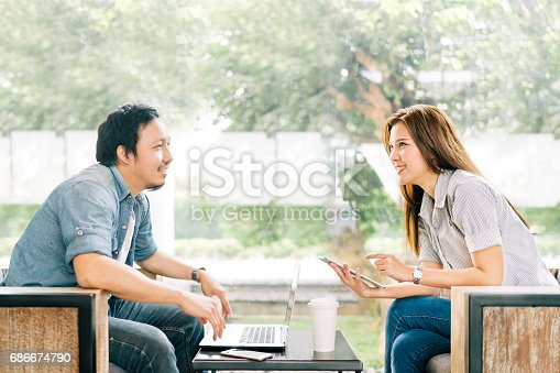 istock Young Asian couple or coworker talking at coffee shop or modern office, garden background. With laptop notebook, smartphone and digital tablet. Modern lifestyle with computer gadget technology concept 686674790