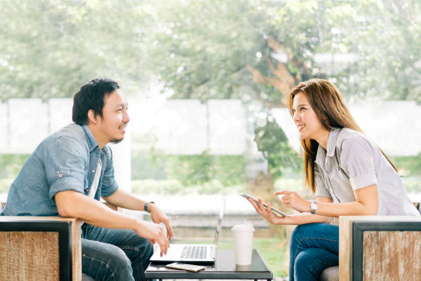 Young Asian couple or coworker talking at coffee shop or modern office, garden background. With laptop notebook, smartphone and digital tablet. Modern lifestyle with computer gadget technology concept Young Asian couple or coworker talking at coffee shop or modern office, garden background. With laptop notebook, smartphone and digital tablet. Modern lifestyle with computer gadget technology concept southeast asian ethnicity stock pictures, royalty-free photos & images