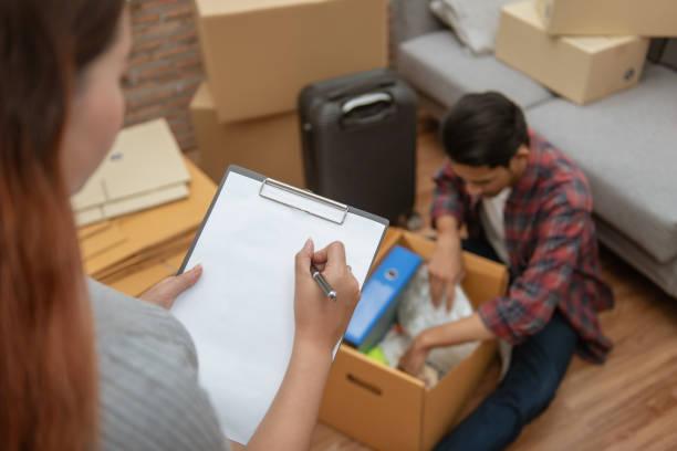 junge asiatische paar packen ihre zugehörigkeit in karton mit einer checkliste vor dem umzug in neue bewohner oder haus nach dem kauf oder mieten eine neue. - umzug checkliste stock-fotos und bilder