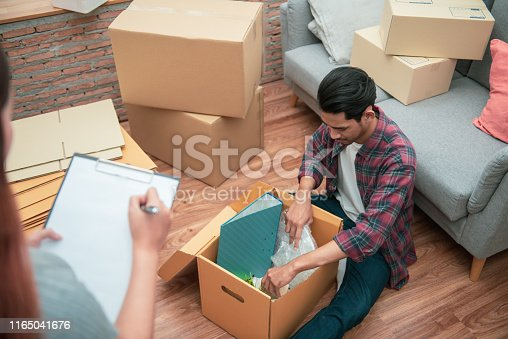 istock Young Asian couple packing their belonging into cardboard box by using a check list before moving to new resident or house after buy or rent a new one. 1165041676