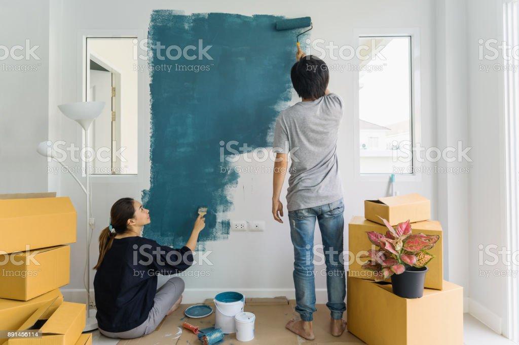 Junge asiatische paar Malerei Innenwand mit Farbroller in neues Haus – Foto