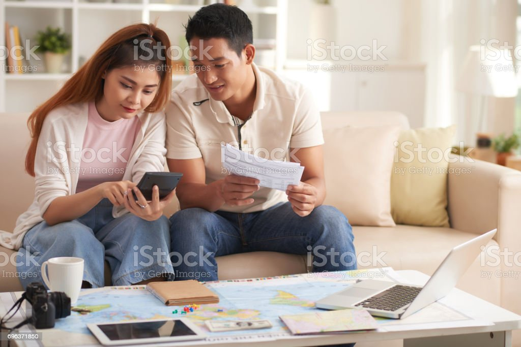 Young Asian Couple Planning Vacation Budget stock photo
