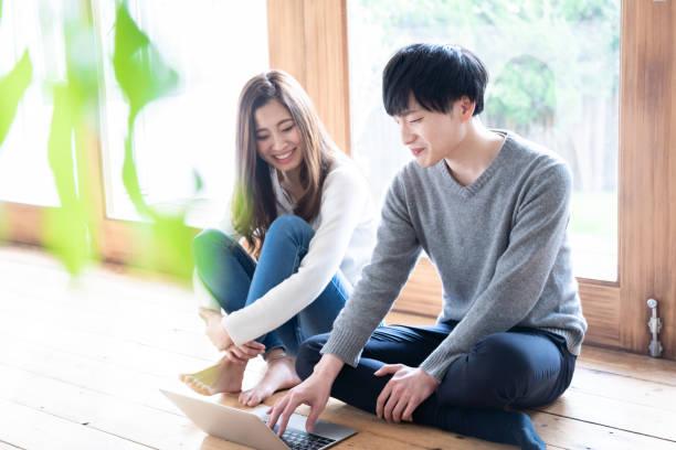 リビングルームでリラックス若いアジアのカップル - ライフスタイル ストックフォトと画像