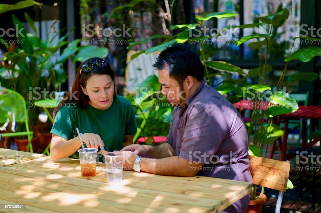 Young Asian Couple sharing information on a mobile phone, at a outdoor café. stock photo