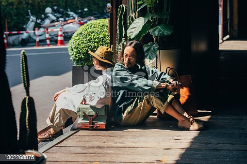 A cute Thai couple sitting back to back in the street, dressed in vintage clothes.