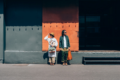 A young Asian couple dressed in vintage clothes, standing in the street and looking in the opposite direction.