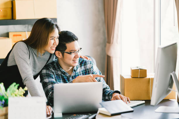 Young Asian couple startup family business, online marketing packaging and delivery scene. SME entrepreneur, business partner, or freelance work at home concept stock photo