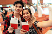 Young asian couple taking selfie with passport and boarding pass