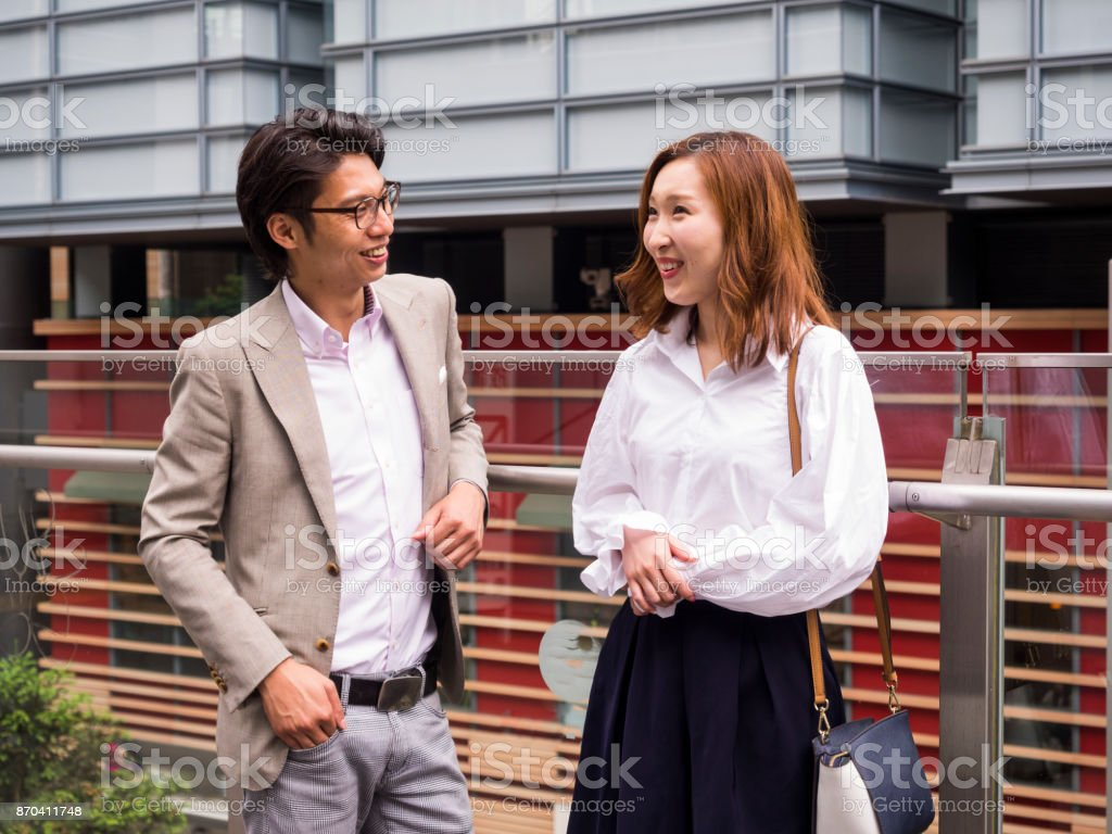 A young Asian couple talks happily in the street. stock photo
