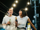 Young asian women toasting drinks with her boyfriend at a rooftop party. Young asian couple hanging out with drinks.
