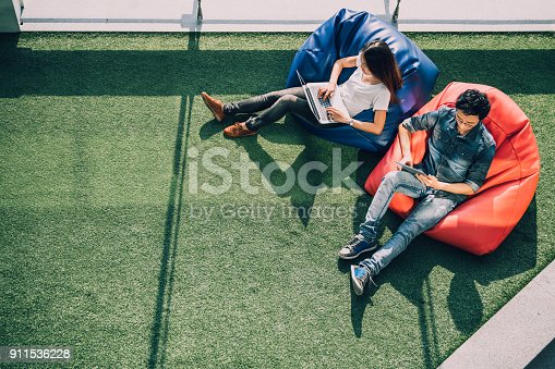 istock Young Asian couple using laptop notebook and digital tablet together in modern public park, sit on bean bag, top view with copy space on grass. Information technology gadget or casual business concept 911536228