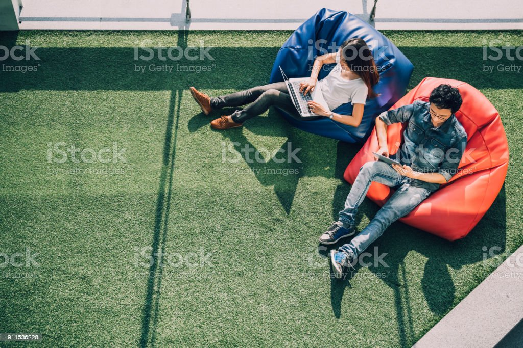 Young Asian couple using laptop notebook and digital tablet together in modern public park, sit on bean bag, top view with copy space on grass. Information technology gadget or casual business concept stock photo