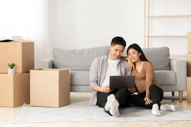 Young asian couple using laptop sitting on floor Online Ordering Concept. Asian family using laptop sitting on floor among boxes, empty space filipino ethnicity stock pictures, royalty-free photos & images