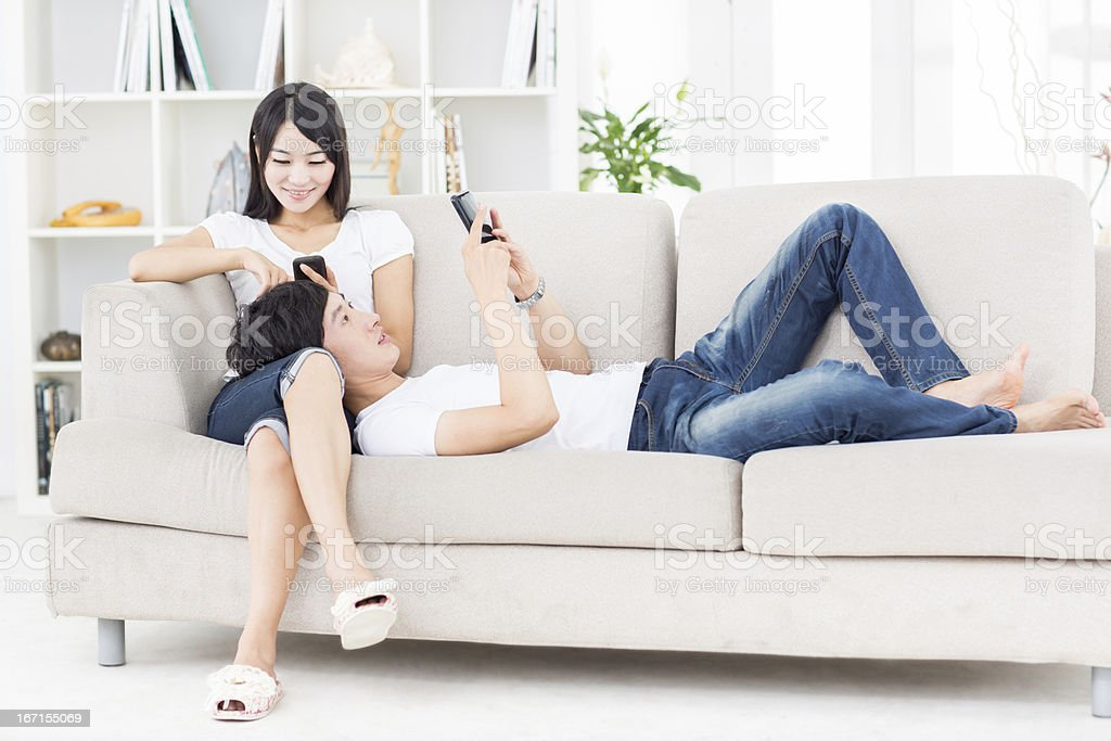 Young Asian couple using phones stock photo