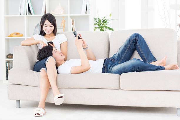 若いアジアカップルを使用して電話 - ガールフレンド ストックフォトと画像