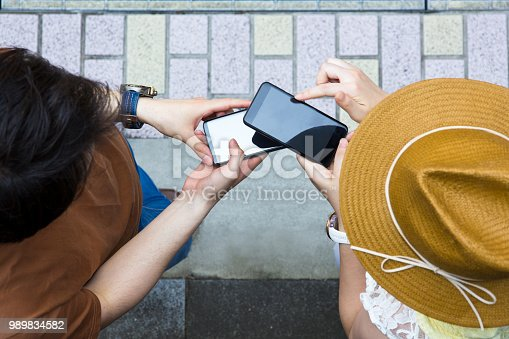Young Japanese woman adding male friend to her LINE friends list by reading his QR Code.