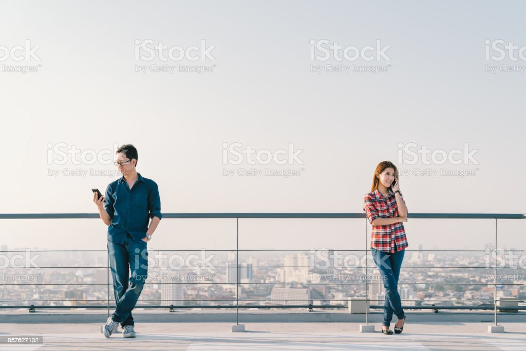 Young Asian couple using telephone call and smartphone together on building roof. Mobile cellphone device or information technology telecommunication concept. Cityscape view background, sky copy space stock photo