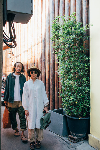 A cute Thai couple wandering around the city in vintage clothes, carrying hand bags