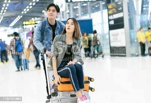 842907838 istock photo Young Asian couples who are happy in the passenger Hall. Men are pushing airport shuttle with a suitcase and a cheerful girl who is sitting on it. While waiting out the journey. 1152151964
