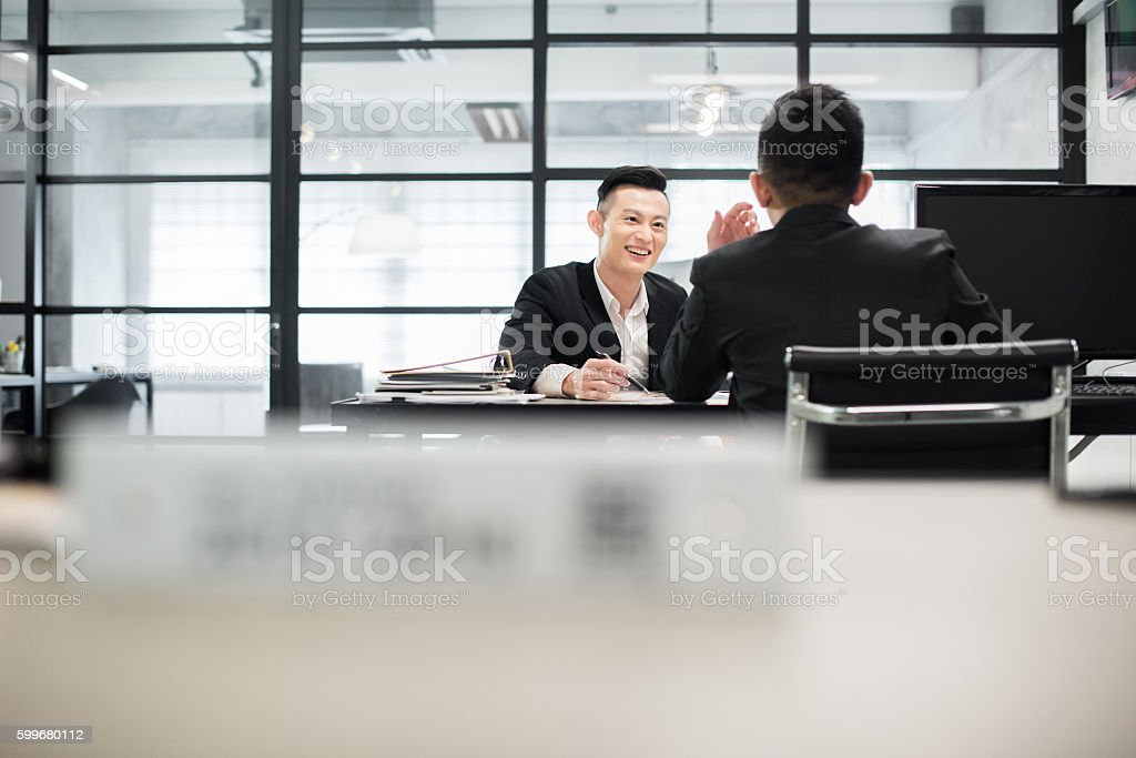 Young Asian coworkers discussing work in the office. stock photo