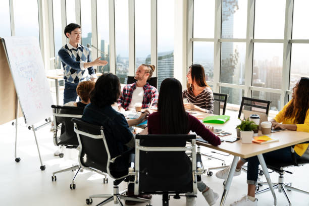 young asian creative businessman standing and making presentation at modern office happy talking and brainstorming with team. casual people business meeting concept. - training imagens e fotografias de stock
