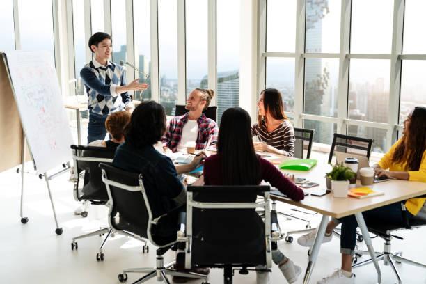 jeune asiatique entrepreneur créatif permanent et en créant la présentation au bureau moderne heureux de parler et de réflexion avec l'équipe. concept de réunion d'affaires occasionnel de la personnes. - dressage photos et images de collection