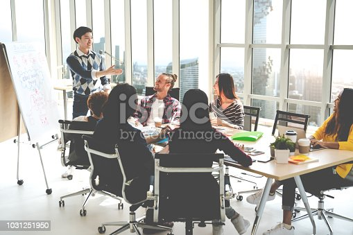 1031237974 istock photo Young asian creative businessman standing and making presentation at modern office happy talking and brainstorming with teamwork on rear view and soft tone. Casual people business meeting concept. 1031251950