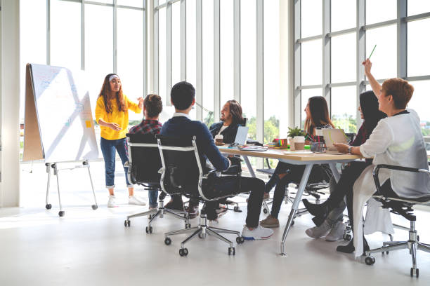 young asian creative hipster female leader standing and making presentation at modern office happy talking marketing idea with team. casual asian people business meeting workshop soft tone concept. - training imagens e fotografias de stock