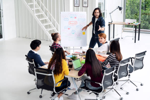 young asian creative man standing and making presentation at modern office happy talking and brainstorming with team. casual multiethnic diverse people business meeting concept with rear view. - training imagens e fotografias de stock