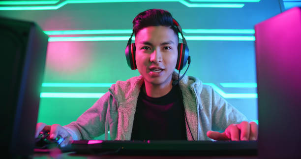 若いアジアのサイバースポーツゲーマー - ゲーム ヘッドフォン ストックフォトと画像