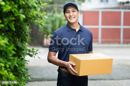 istock Young asian delivery man smiling while holding a cardboard box delivery to his customer. 848475436