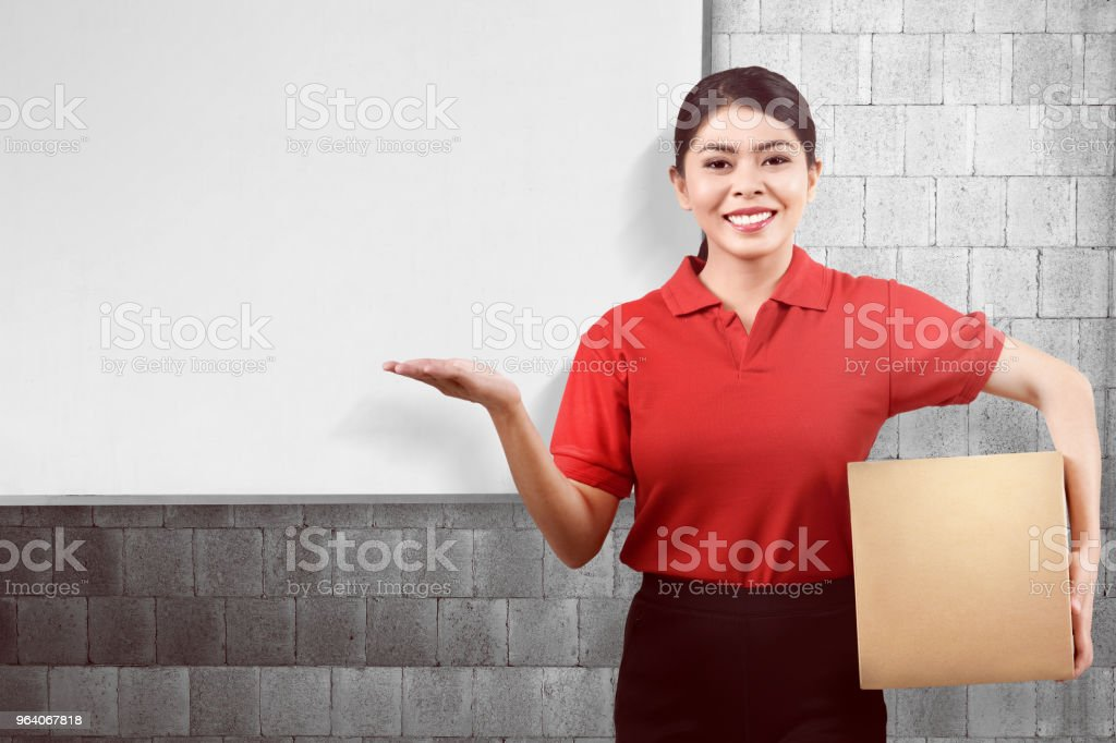 Young asian delivery woman carrying parcel and showing copyspace - Royalty-free Adult Stock Photo