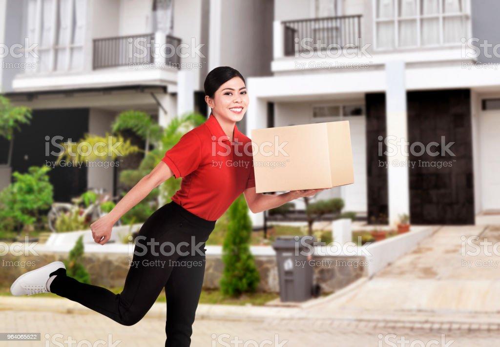 パッケージを配布する若いアジア配達の女性 - 1人のロイヤリティフリーストックフォト