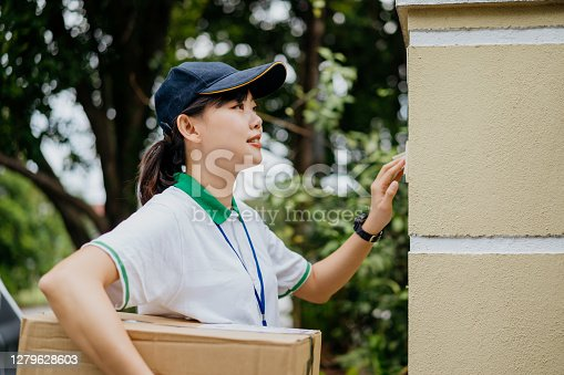 Young Asian delivery woman smiling while holding a cardboard box and pressing doorbell to notify her customer