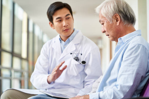 young asian doctor explaining medical condition to senior patient in hospital stock photo