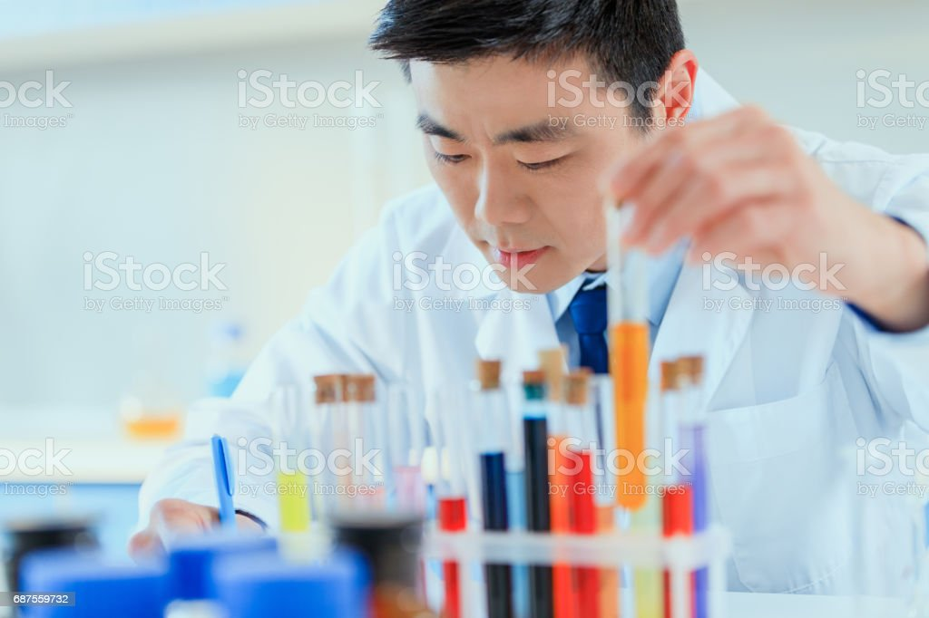 young asian doctor in uniform working at testing laboratory, chemical laboratory stock photo