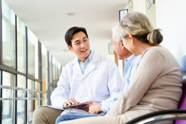 young asian doctor talking to senior patients in hospital stock photo
