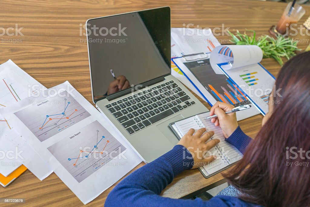 Young Asian employee writing important information from laptop to notes stock photo