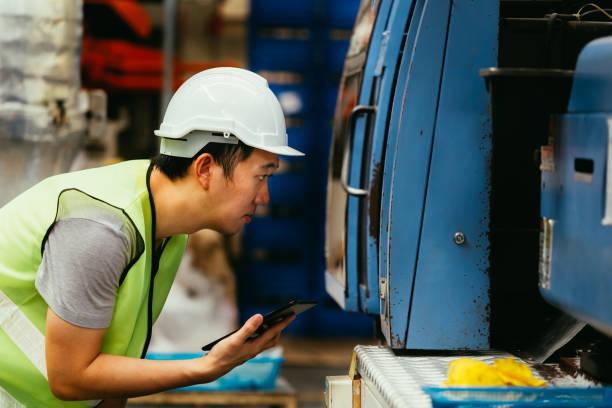 Young Asian engineer inspecting machine in factory stock photo