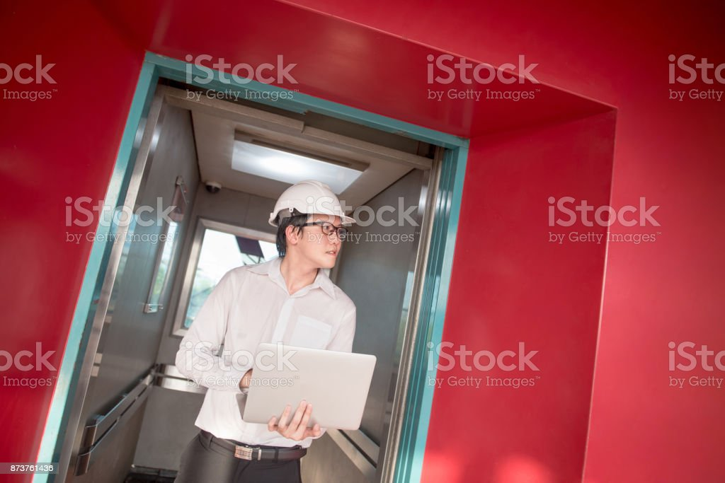 Young Asian engineer or architect holding laptop computer in elevator that surrounded by red wall stock photo
