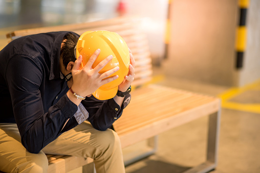 istock Young Asian engineer or architect man feeling tried and worried while sitting on bench 957669660