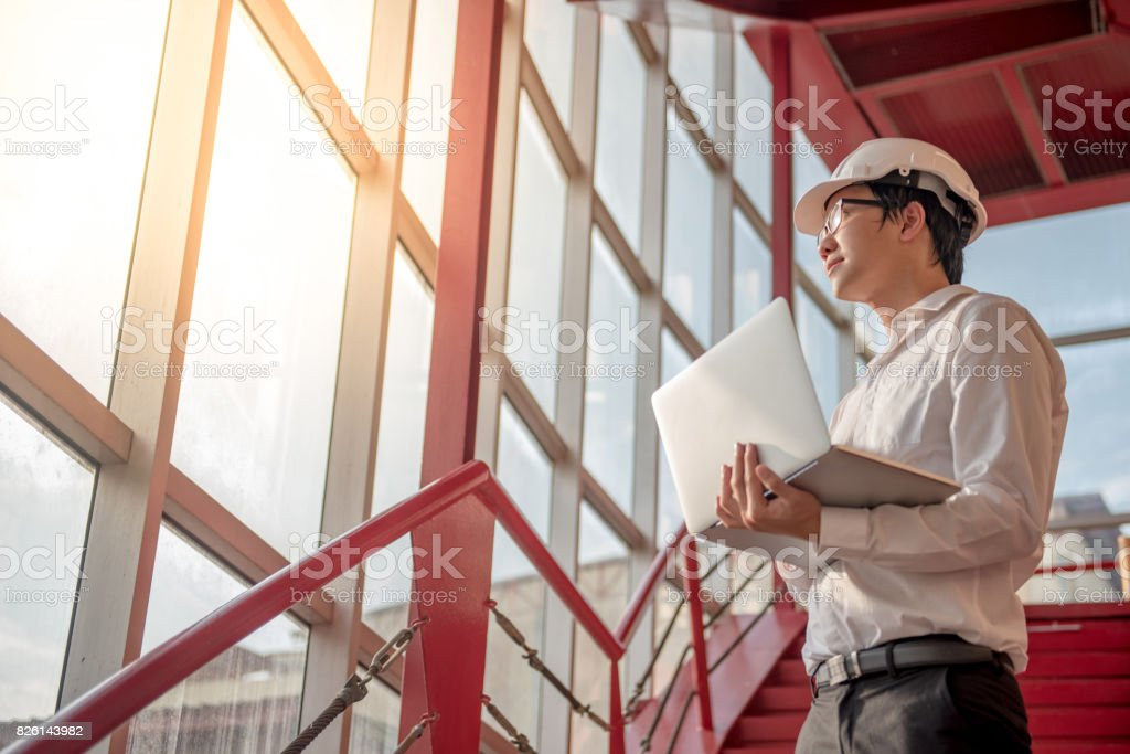 Young Asian Engineer or Architect working with laptop stock photo