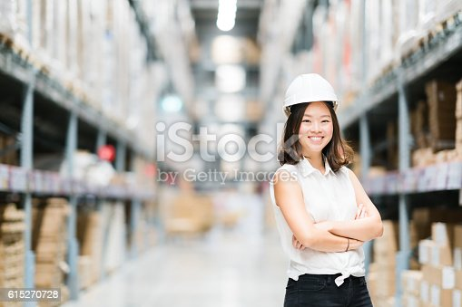 istock Young Asian engineer or technician smiling, warehouse blur background 615270728