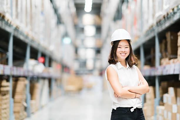 young asian engineer or technician smiling, warehouse blur background - kreativer speicher stock-fotos und bilder