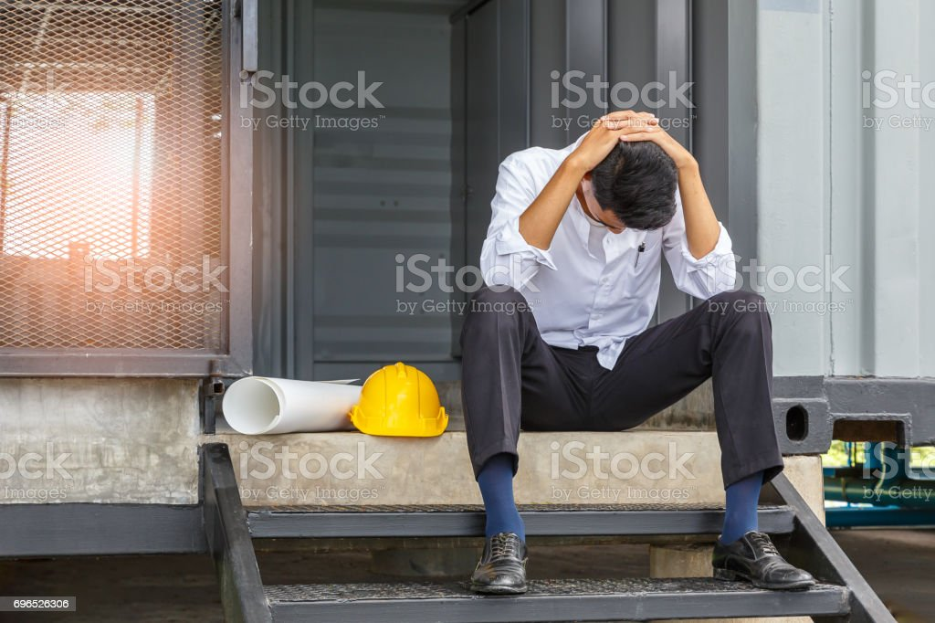 Young asian engineer suffering stress working at construction site stock photo
