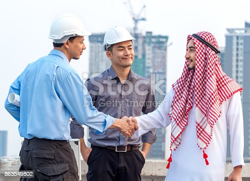1071990712 istock photo Young asian engineer/architect shaking hands with arab businessman, talking discussing about a project construction building, teamwork, togetherness, positive feeling concept 863549802