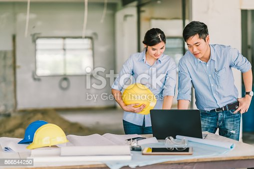 1166176793 istock photo Young Asian engineers couple work together using notebook computer at building construction site. Civil engineering brainstorm meeting, architecture design, or house builder concept. With copy space 866544250