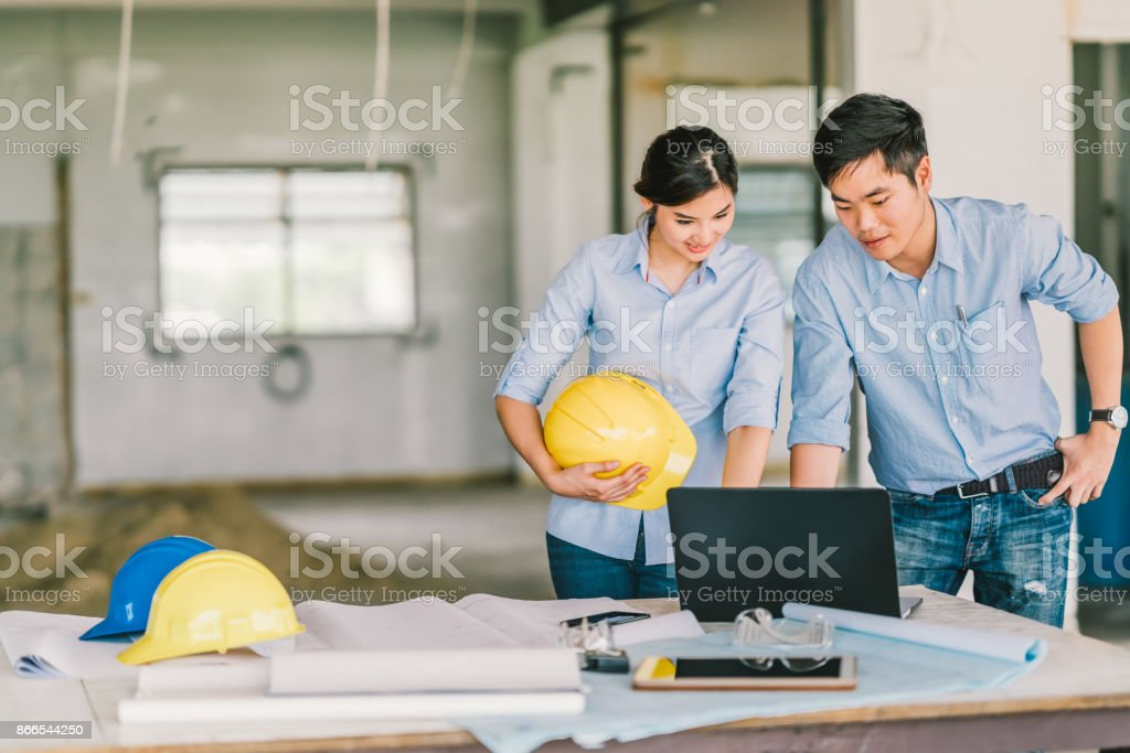 Young Asian engineers couple work together using notebook computer at building construction site. Civil engineering brainstorm meeting, architecture design, or house builder concept. With copy space stock photo