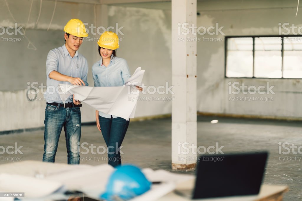 Young Asian Engineers Couple Working On Building Blueprint At Construction  Site. Civil Engineering, Industrial