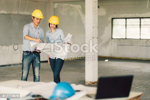 1166176793 istock photo Young Asian engineers couple working on building blueprint at construction site. Civil engineering, industrial, or home renovation concept. With copy space 812773676